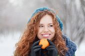 Beautiful Girl In Blue Beret Holds Mandarin And Looks Away At Winter Day In Park