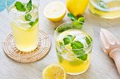 stock photo of mints  - Lemonade with fresh lemon and mint by lemon reamer - JPG