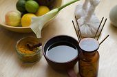 stock photo of massage oil  - A countertop arrangement of ayurvedic turmeric spice oil and massaging tools and an exotic flower used in Ayurveda massage - JPG