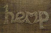 The Word Hemp Written Artistically In Hemp Seeds On A Wooden Chopping Board
