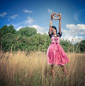 Young woman wearing dirndl posing in the field with pretzel
