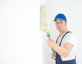 image of overhauling  - Painter in uniform paints the wall - JPG