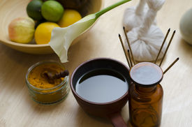 stock photo of vedic  - A countertop arrangement of ayurvedic turmeric spice oil and massaging tools and an exotic flower used in Ayurveda massage - JPG