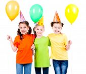 Portrait of three cute little girls with color balloons and party hat - isolated on a white.