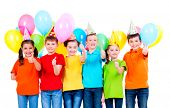 Group of happy children in colored t-shirts and party hats with balloons showing thumbs up sign on a