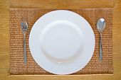White Empty Dish With Spoon And Fork Set On Thai Mat Wooden Desk