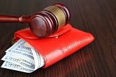 Gavel and money in wallet on wooden background