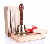 Gold retro school bell with scroll and books isolated on white