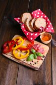 Composition with knife,  tasty salami sausage, sliced bread and pepper on cutting board, on wooden background