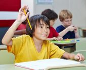 Japanese elementary school student raising his hand in class
