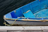 foto of lobster boat  - Colorful blue wooden row boat tied to dock with dark waves water - JPG