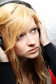 Blonde girl listening music with headphones