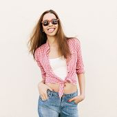 picture of sticking out tongue  - Young woman in sunglasses posing by the wall - JPG