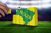 Hand building wall of green brazil outline on yellow with text