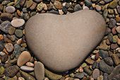 a heart-shaped stone on naturally polished color rock pebbles background