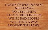 Good people do not need laws to tell them to act responsibly, while bad people will find a way around the laws  - quote on wooden red oak background
