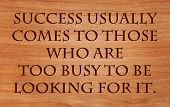 Success usually comes to those who are too busy to be looking for it - quote on wooden red oak backg