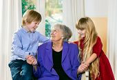 Loving Little Boy And Girl With Their Grandmother