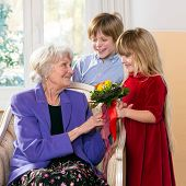 Children Giving Grandmother Flowers