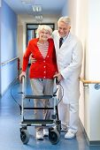 Physician Helping A Senior Woman In A Walker
