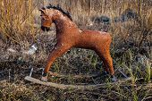 stock photo of dump  - Old threadbare rocking horse thrown away to the dump in the field - JPG