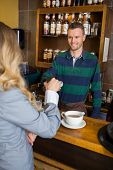 Young male bartender holding card-reader while woman making payment through cellphone at coffeeshop