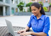 stock photo of indian blue  - Closeup portrait young pretty woman in blue shirt resting hands on keyboard browsing digital computer laptop isolated background of sunny outdoor green trees office background - JPG