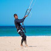 handsome athlete prepares his kite for kitesurfing training