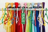 stock photo of outfits  - Sale sign for summer clothes on a clearance rack with colorful summer outfits and accessories - JPG