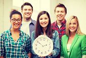 education concept - group of students at school with clock