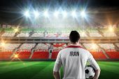 Iran football player holding ball against stadium full of iran football fans