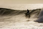 Young Male Riding A Wave On His Paddle-ski