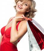 portrait of attractive  caucasian smiling woman blond isolated on white studio shot lips toothy smile  hair head and shoulders looking at camera in red dress shopping bags sale