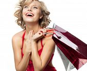 portrait of attractive  caucasian smiling woman blond isolated on white studio shot lips toothy smile face hair  looking up laughing red dress figure shopping bags sale