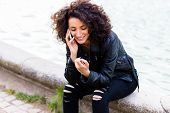 African woman telephoning with mobile phone at city fountain