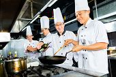 Chefs in Asian Restaurant kitchen cooking