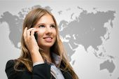 Smiling woman talking on the phone in front of a world map