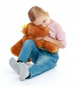 Little girl hugging a teddy bear.