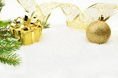 Golden Christmas Baubles With And Needles Fir And Ribbon On Snow