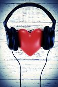 Headphones and heart on wooden background