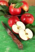 Ripe apples in bowl with knife on wooden background
