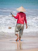 Lone fisherman on beach in the morning in Bali Indonesia