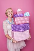 Laughing blonde woman holding big and small colorful gift boxes. Soft colors. Christmas, birthday, V