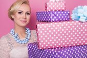 Woman with colorful jewelry holding big and small present boxes. Soft colors. Christmas, birthday