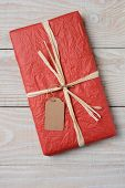 High angle image of a red tissue wrapped Christmas present on a rustic white wood kitchen table. The gift is tied with raffia and has a blank gift tag. Vertical Format.