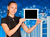 Beautiful businesswoman in dress holding tablet pc. Network, buildings and world map as backdrop
