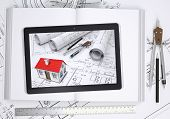 Small house with drawings displayed on tablet screen. Open book and tools of architect