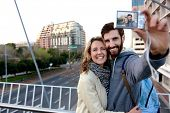 couple taking selfie photograph in city on vacation
