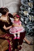 Child with mother receiving near Christmas tree. Retro style.