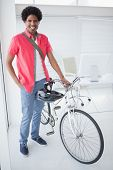 Smiling businessman standing with his bike in his office